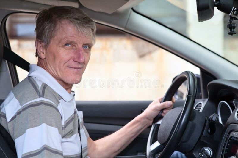 Il maschio maturo del driver con esperienza tiene il volante immagine stock libera da diritti