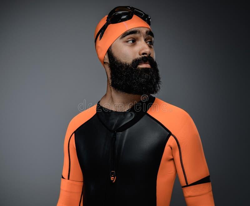 Il maschio nella maschera di immersione con bombole e l'arancia neopren la muta subacquea immagine stock