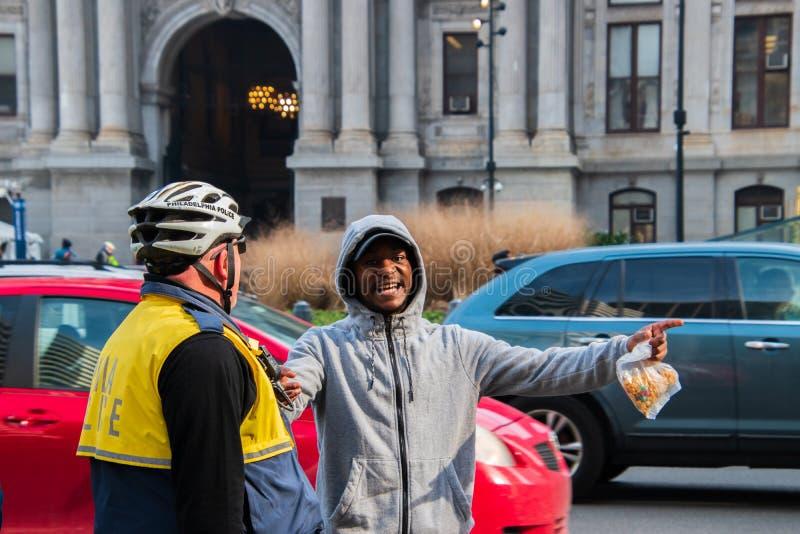 Il maschio nero è qui scherzare visto con un ufficiale di polizia di Filadelfia fotografia stock