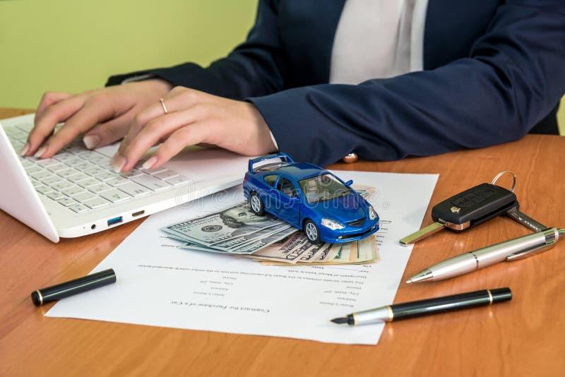Il ` maschio s passa la firma sulla forma di reclamo del contratto dell'automobile e sul calcolatore, dollaro fotografia stock