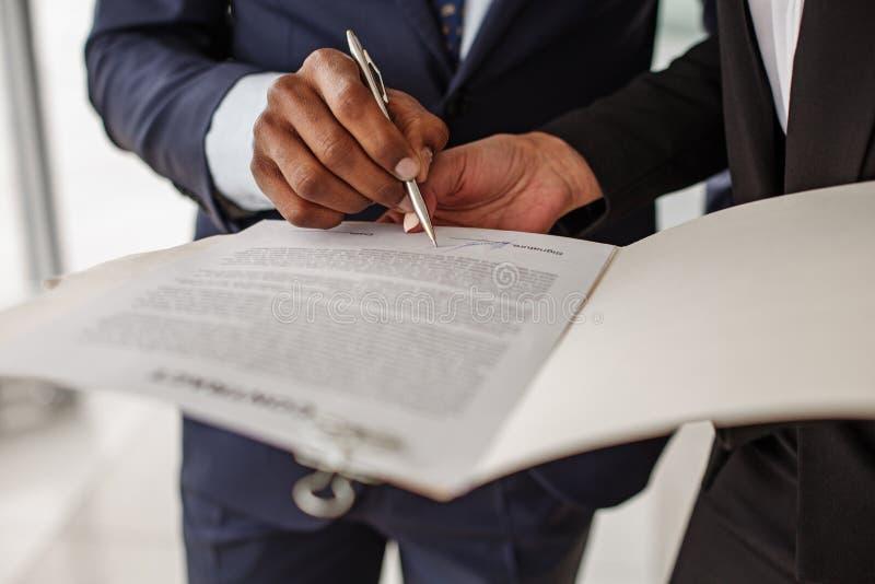Il maschio sta mettendo la sua firma nell'accordo immagine stock