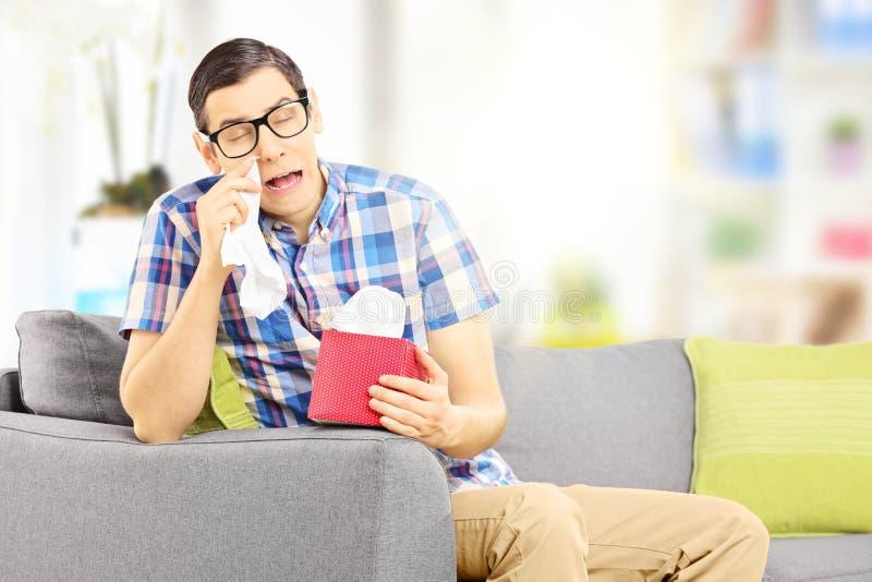 Il maschio triste su un sofà che pulisce il suo osserva dal gridare a casa fotografie stock