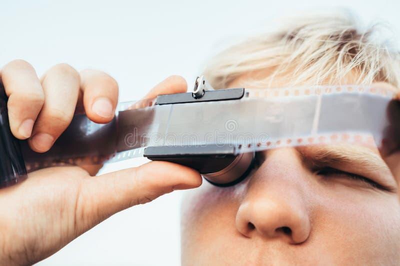 Il maschio usa il vecchio spettatore del negativo di film dell'annata 35mm per vedere un fra fotografia stock