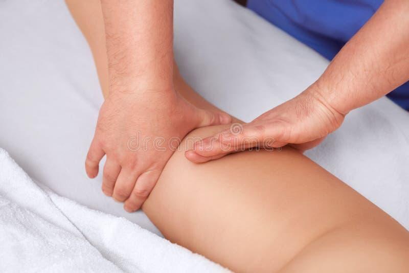 Il massaggiatore fa il massaggio delle Anti-celluliti sulla natica e sulle coscie del paziente immagine stock libera da diritti
