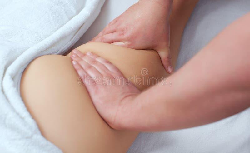 Il massaggiatore fa il massaggio delle Anti-celluliti sulla natica e sulle coscie del paziente fotografie stock libere da diritti
