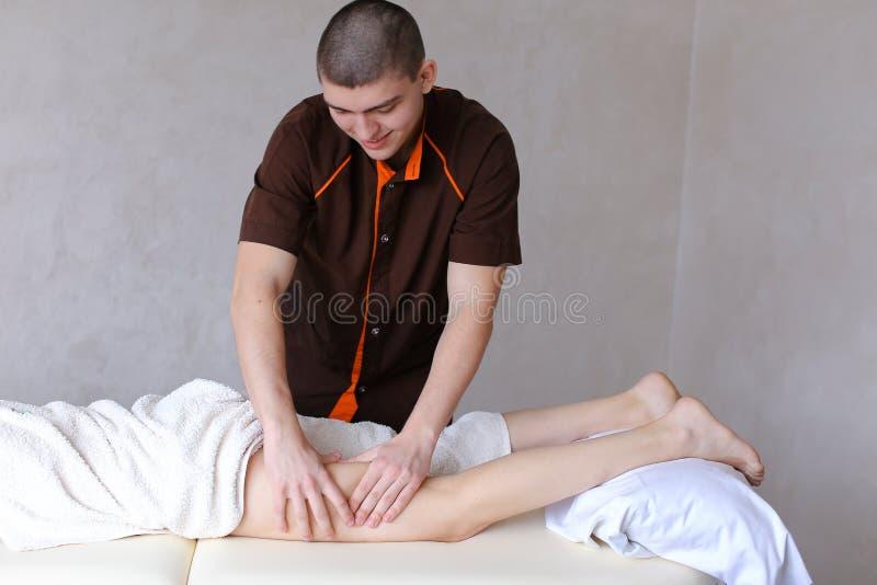 Il massaggiatore maschio professionista impasta le gambe della ragazza al paziente, che Li fotografia stock