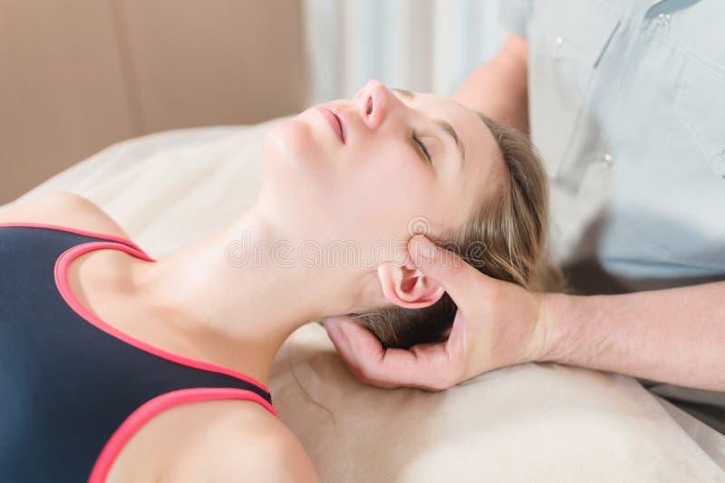 Il massaggiatore viscerale manuale maschio del terapista cura un giovane paziente femminile Massaggio dell'orecchio e della testa fotografie stock