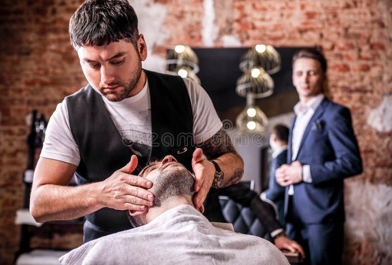 Il Master apporta la rettifica delle barbe nel salone del parrucchiere Chiuda sulla foto fotografia stock
