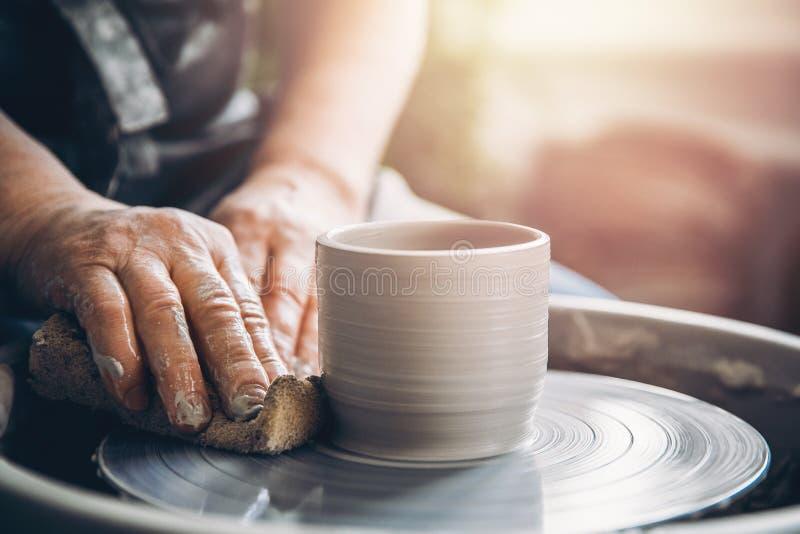 Il Master sul tornio da vasaio fa i piatti dell'argilla Posto dell'officina fotografia stock libera da diritti