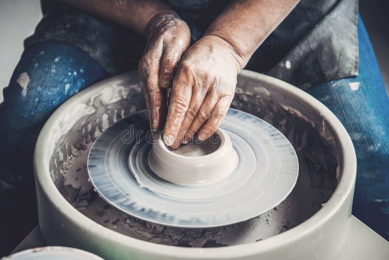 Il Master sul tornio da vasaio fa i piatti dell'argilla Posto dell'officina immagine stock