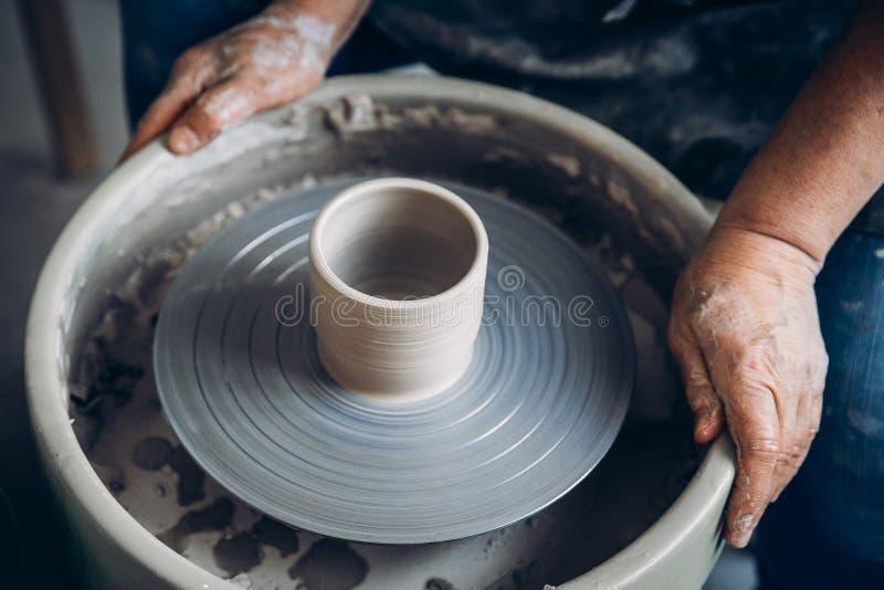 Il Master sul tornio da vasaio fa i piatti dell'argilla Posto dell'officina fotografia stock