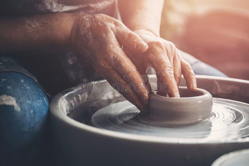 Il Master sul tornio da vasaio fa i piatti dell'argilla Posto dell'officina immagini stock