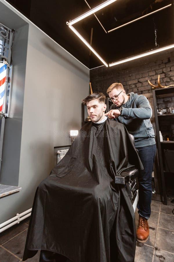 Il Master taglia i capelli e la barba degli uomini nel parrucchiere, parrucchiere fa l'acconciatura per un giovane Lavoro del bar fotografia stock