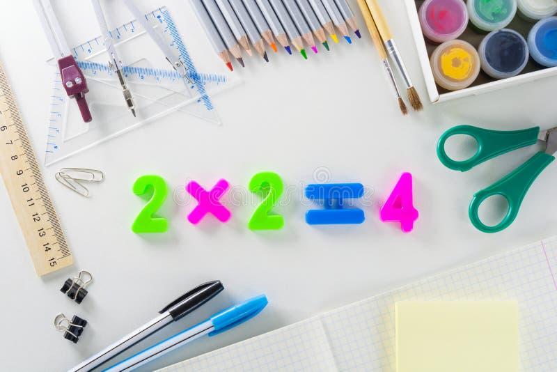 Il ` matematico del ` 2*2=4 di equazione dai numeri di plastica su un fondo bianco con gli articoli della scuola fotografie stock