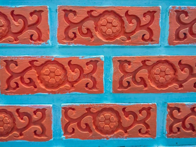 Il mattone rosso luminoso con l'edera del fiore ha modellato il fondo della parete immagine stock