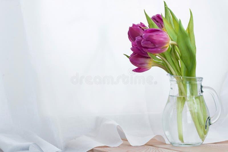 Il mazzo dei tulipani rosa in un decantatore di vetro su una tavola di legno immagine stock libera da diritti