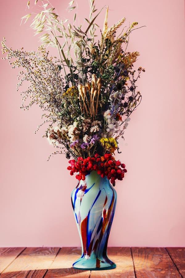 Il mazzo del campo ha asciugato i fiori in vaso blu d'annata fotografie stock