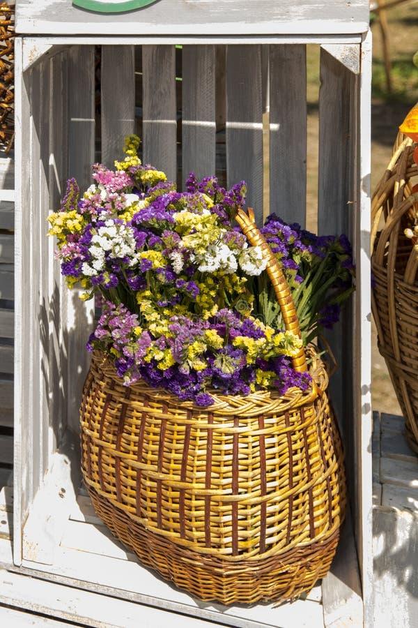 Il mazzo dell'autunno blu, giallo e bianco fiorisce in un canestro immagini stock libere da diritti