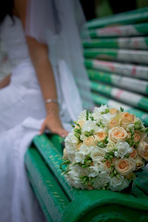 Il mazzo della sposa si trova su un banco verde immagini stock