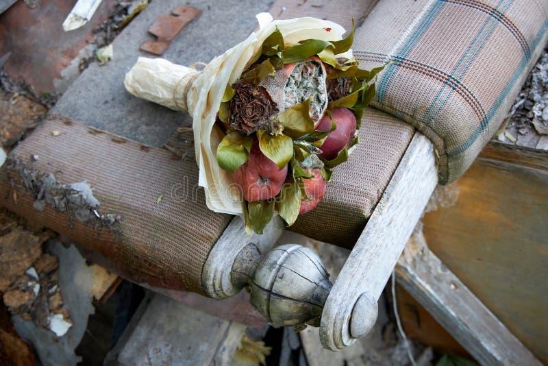 Il mazzo di frutta marcia ed i fiori appassiti mettono sui resti di mobilia rotta fotografia stock libera da diritti