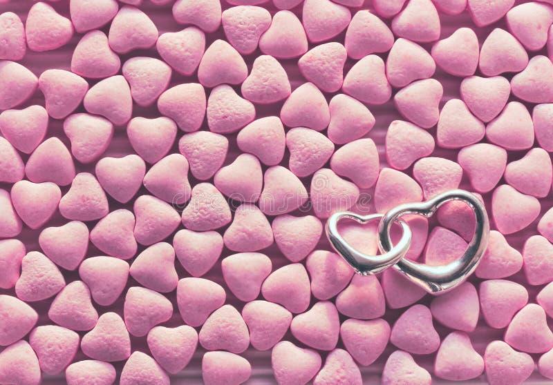 Il mazzo di poca caramella rosa ha sparso, cuori d'argento del pendente due immagine stock