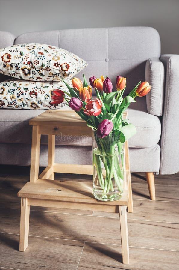 Il mazzo fresco dei tulipani in vaso è in salone Decorazione domestica accogliente fotografia stock libera da diritti
