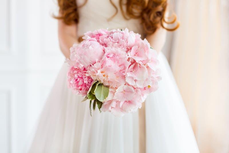 Il mazzo nuziale bello di nozze rosa fiorisce in mani della sposa fotografia stock libera da diritti