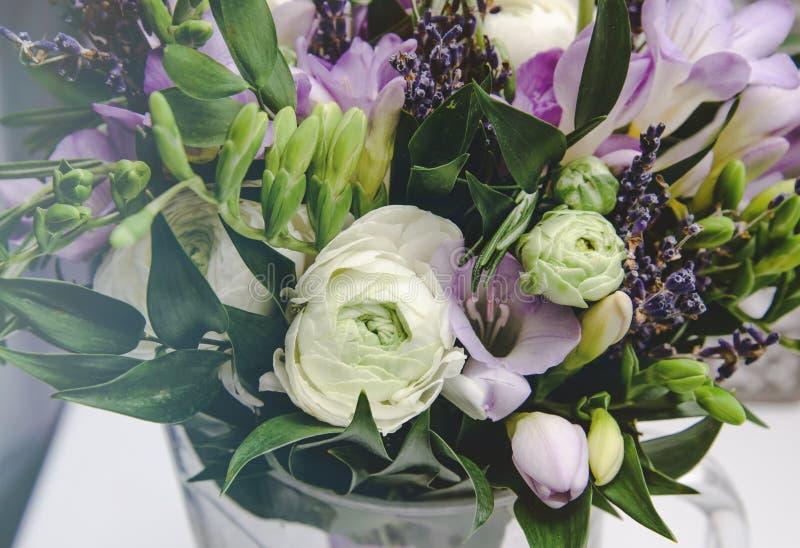 Il mazzo ricco di fresia bianco del ranunculus e del lillà del ranuncolo, rose fiorisce, foglia verde in vaso di vetro Estate fre fotografia stock
