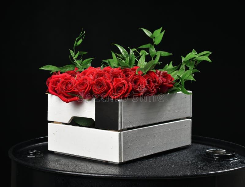 Il mazzo rustico moderno delle rose rosse in scatola di legno e nel verde copre di foglie o fotografia stock libera da diritti