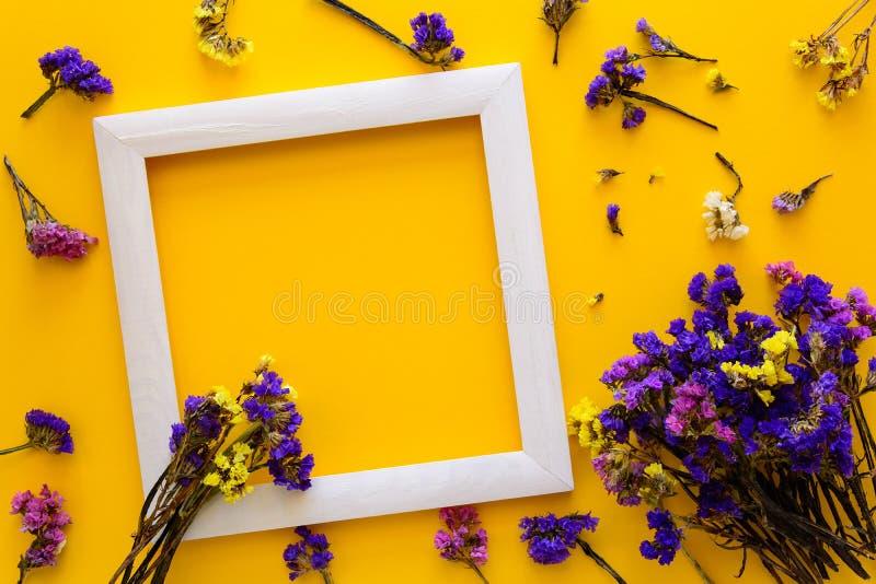 Il mazzo variopinto dell'autunno secco fiorisce la menzogne su una struttura bianca su fondo di carta giallo Copi lo spazio Dispo fotografia stock libera da diritti