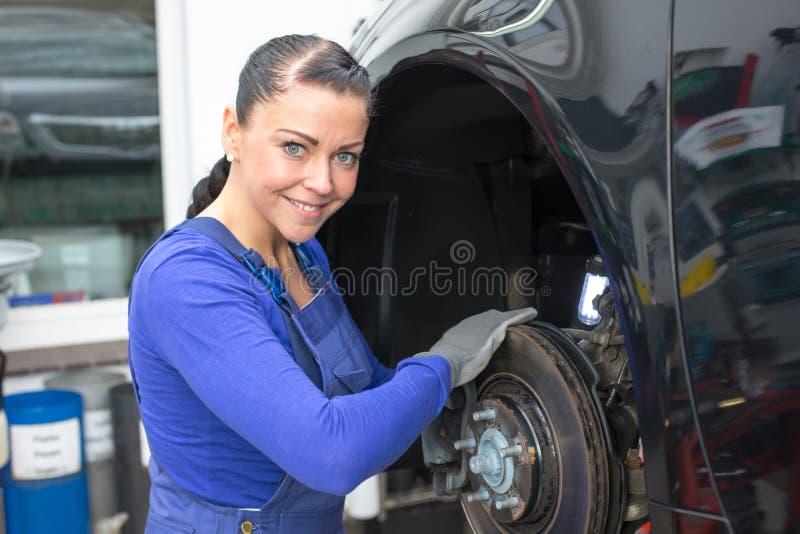 Il meccanico di automobile ripara i freni fotografia stock