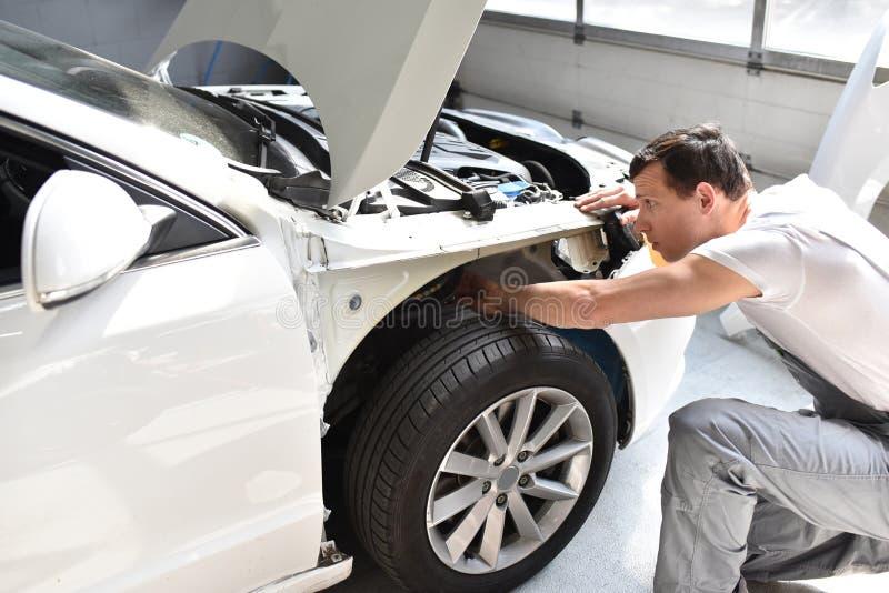 Il meccanico di automobile ripara la carrozzeria dell'automobile di un veicolo dopo un traffico a fotografie stock