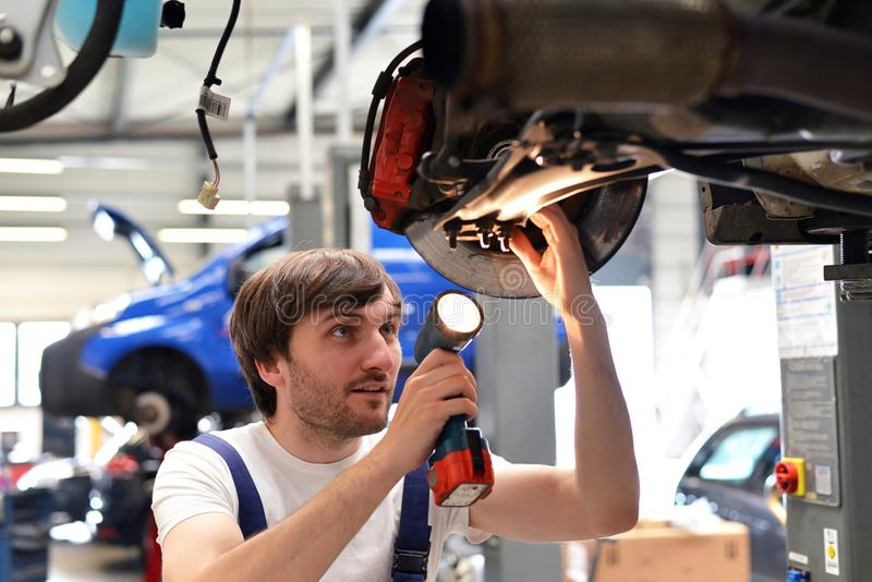 Il meccanico di automobile ripara il veicolo in un'officina fotografia stock