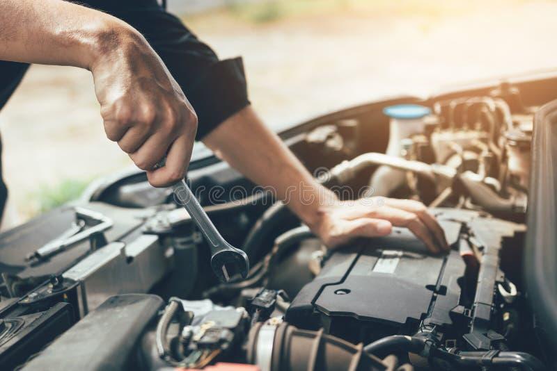 Il meccanico di automobile sta giudicando una chiave pronta a controllare il motore e la manutenzione fotografie stock libere da diritti