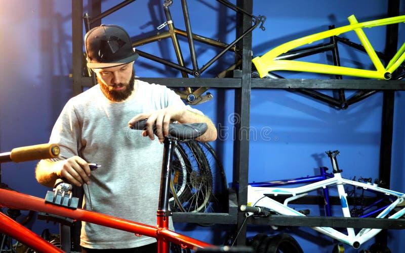 Il meccanico fissa il sedile di bicicletta alla struttura della bicicletta fotografia stock libera da diritti