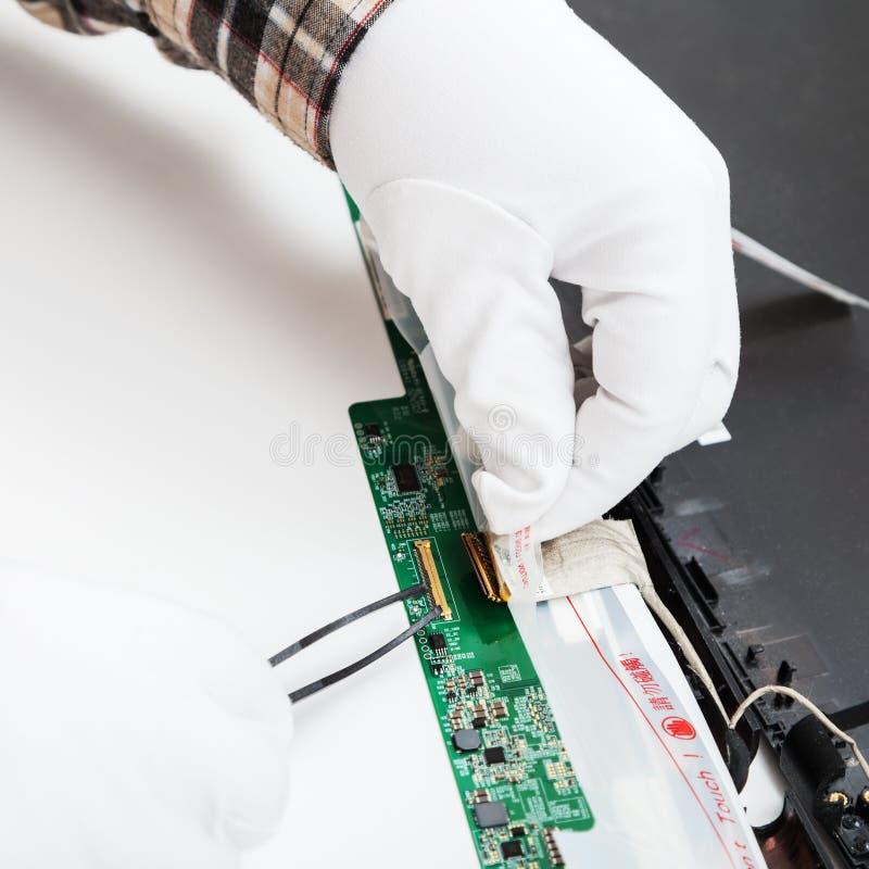 Il meccanico in guanti bianchi sostituisce lo schermo LCD fotografia stock