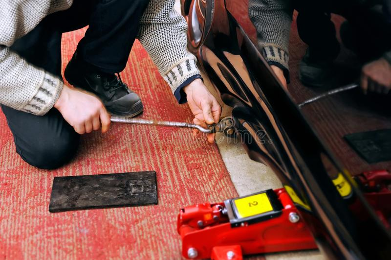 Il meccanico installa un martinetto idraulico meccanico e per la riparazione dell'automobile fotografie stock