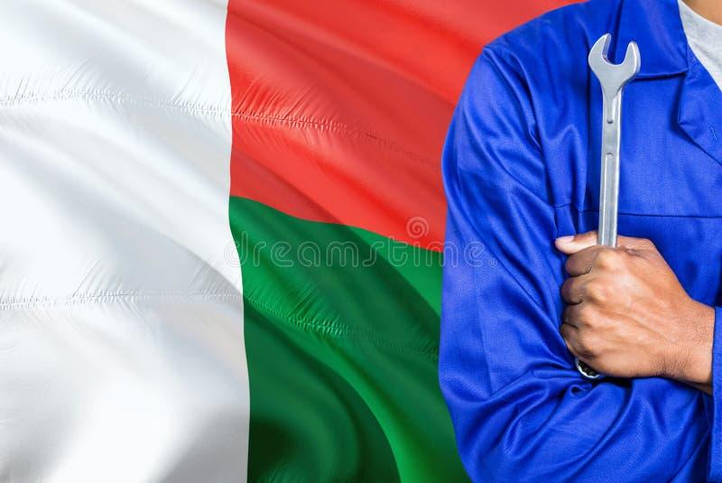 Il meccanico malgascio in uniforme blu sta tenendo la chiave contro l'ondeggiamento del fondo della bandiera del Madagascar Tecni fotografia stock