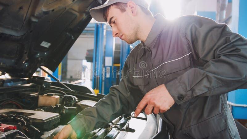 Il meccanico nei controlli di camici livella dell'olio per motori nella riparazione automobilistica di servizio dell'automobile immagini stock