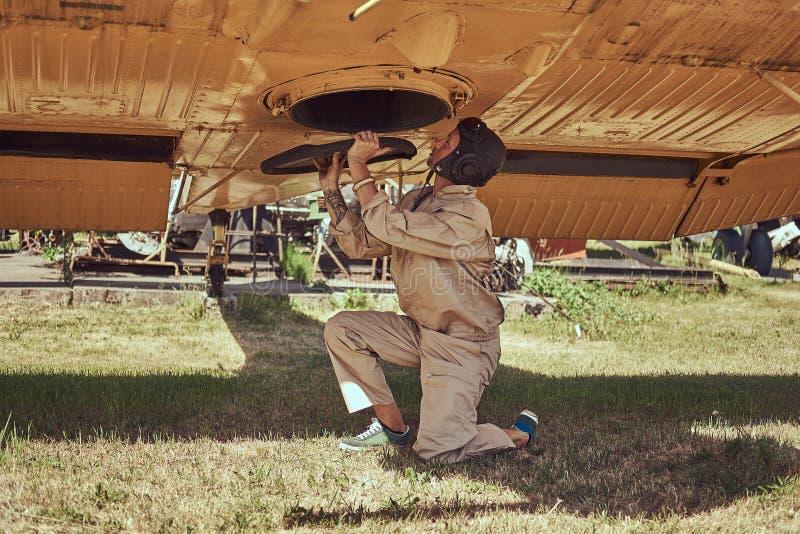 Il meccanico nel casco di volo e dell'uniforme ripara il vecchio aeroplano militare in un museo all'aperto fotografia stock libera da diritti