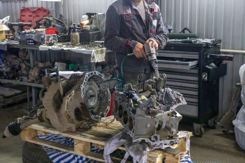 Il meccanico ripara il blocchetto della valvola del ` s del motore dell'automobile in un centro di auto-cura fotografia stock libera da diritti