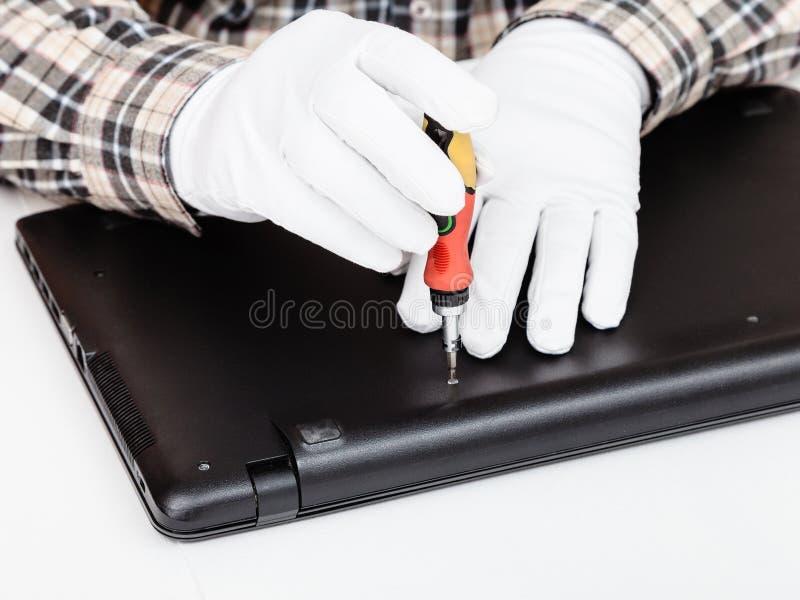 Il meccanico smonta il computer portatile con il cacciavite fotografie stock libere da diritti
