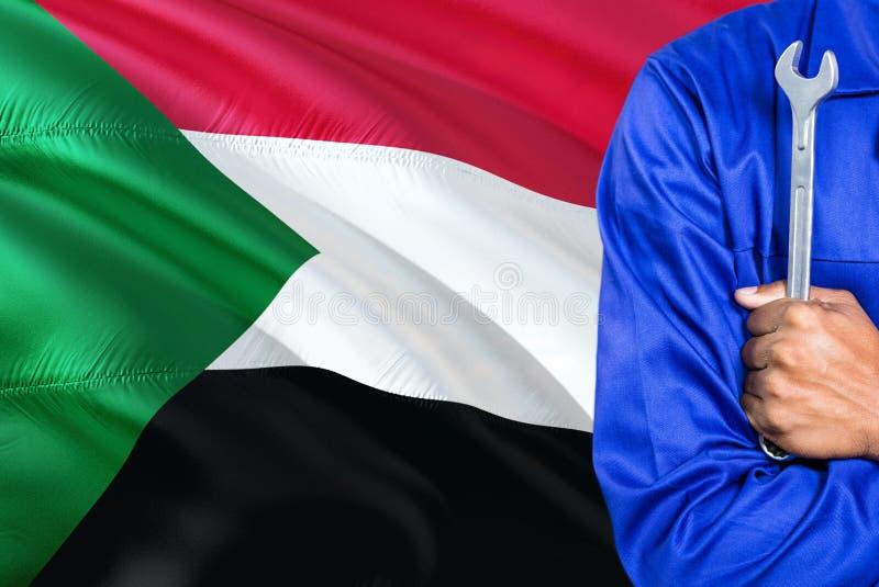 Il meccanico sudanese in uniforme blu sta tenendo la chiave contro l'ondeggiamento del fondo della bandiera del Sudan Tecnico att immagini stock libere da diritti
