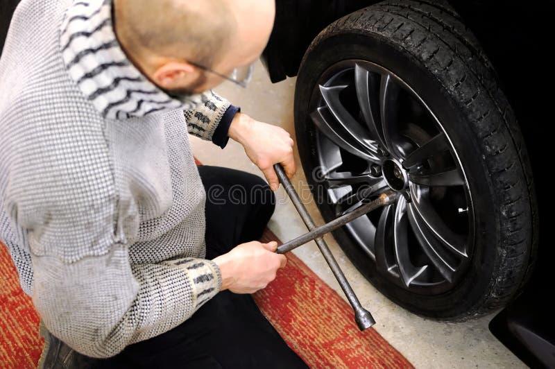 Il meccanico svita i bulloni della ruota con una chiave fotografie stock libere da diritti