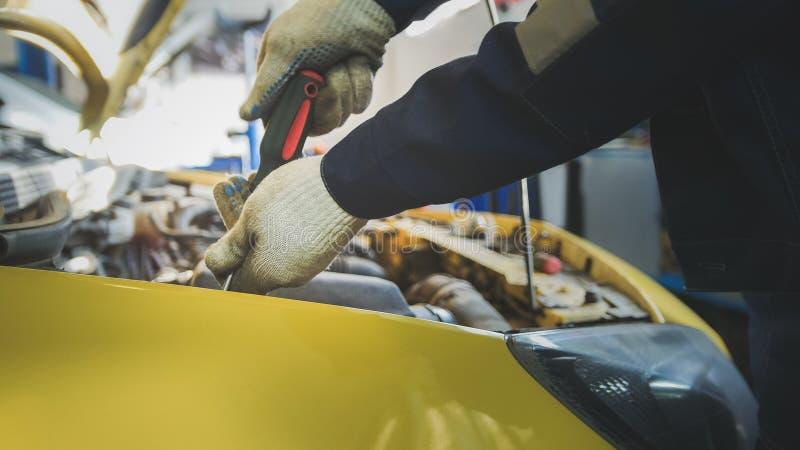 Il meccanico svita il dettaglio dell'automobile in cappuccio - servizio che ripara, alto vicino dell'automobile fotografia stock libera da diritti