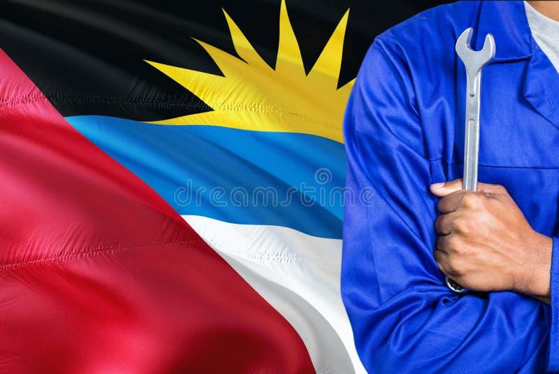 Il meccanico in uniforme blu sta tenendo la chiave contro l'ondeggiamento del fondo della bandiera dell'Antigua e Barbuda Tecnico immagini stock