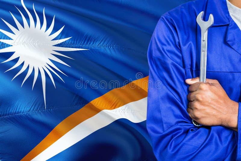 Il meccanico in uniforme blu sta tenendo la chiave contro l'ondeggiamento del fondo della bandiera di Marshall Islands Tecnico at fotografia stock libera da diritti