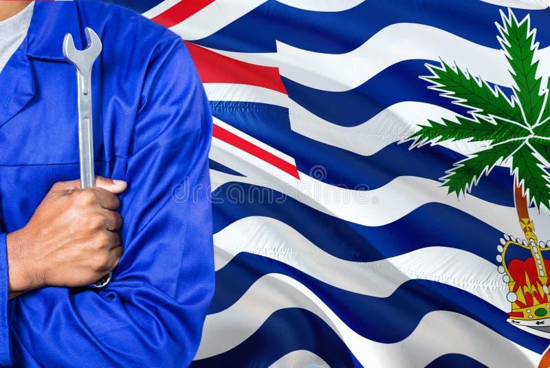 Il meccanico in uniforme blu sta tenendo la chiave contro l'ondeggiamento del fondo della bandiera di Territorio Britannico dell' fotografie stock libere da diritti