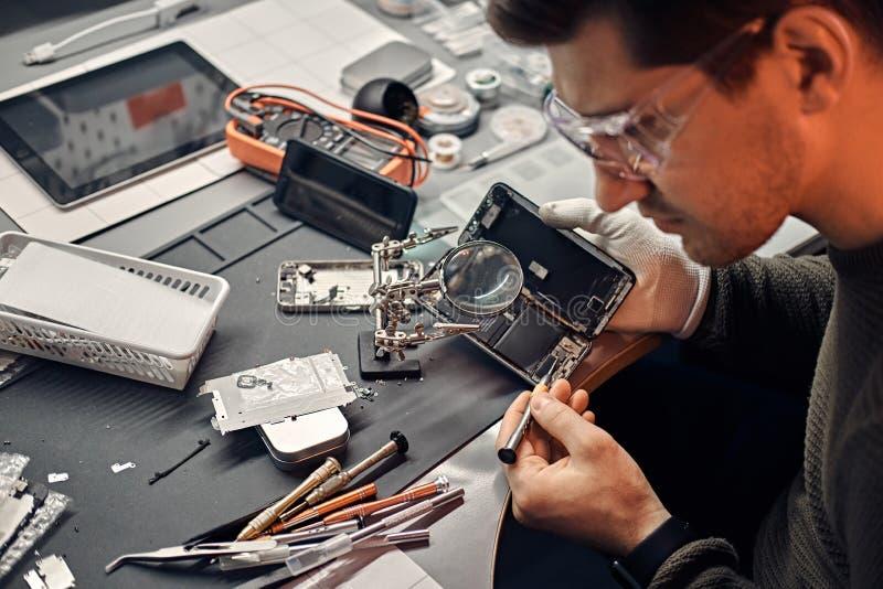 Il meccanico utilizza la lente ed il cacciavite per riparare lo smartphone nocivo nell'officina immagine stock libera da diritti