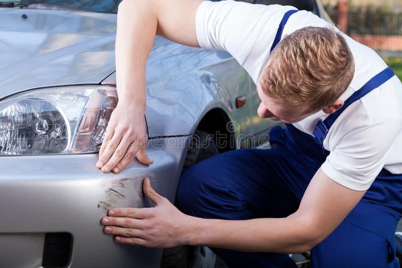 Il meccanico valuta il danno sull'automobile immagine stock libera da diritti